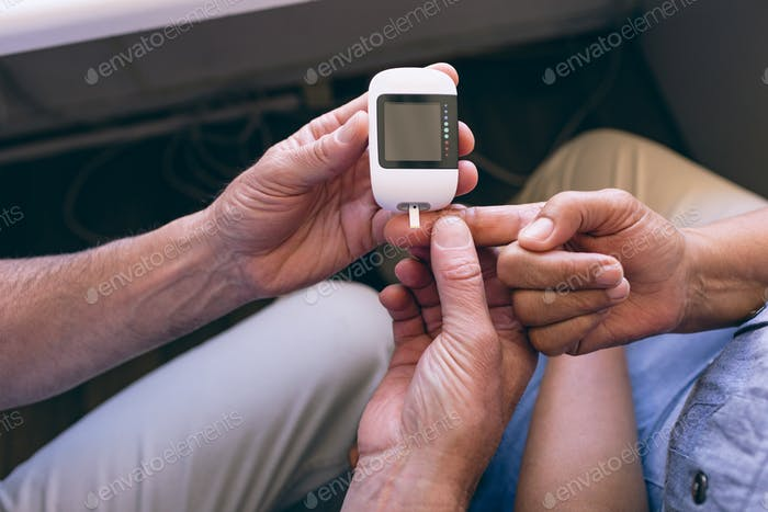 Male doctor examining senior female with glucometer at clinic at retirement home