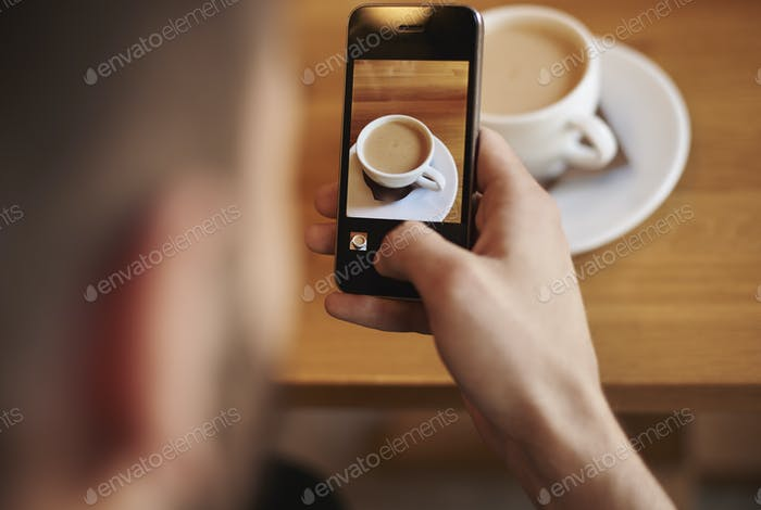 Man taking picture of cup of coffee