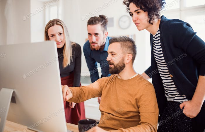 Group of young businesspeople looking at laptop screen in office, discussing issues.