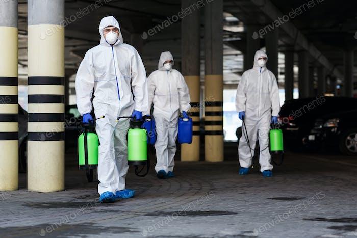 Hombres en trajes protectores de virus que planean desinfectar la ciudad con productos químicos