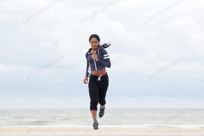 Full body sporty african american woman running by the beach