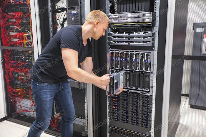 Computer Engineer Installing Blade Server In Datacenter