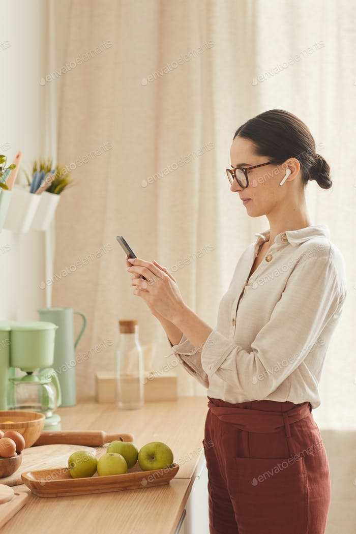 Elegant Adult Woman Using Smartphone at Home