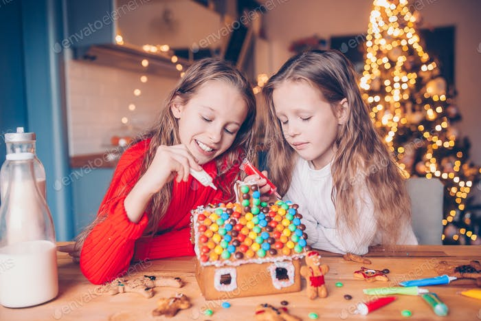 Little girls making Christmas gingerbread house at fireplace in decorated living room