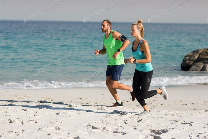 Young couple jogging at beach