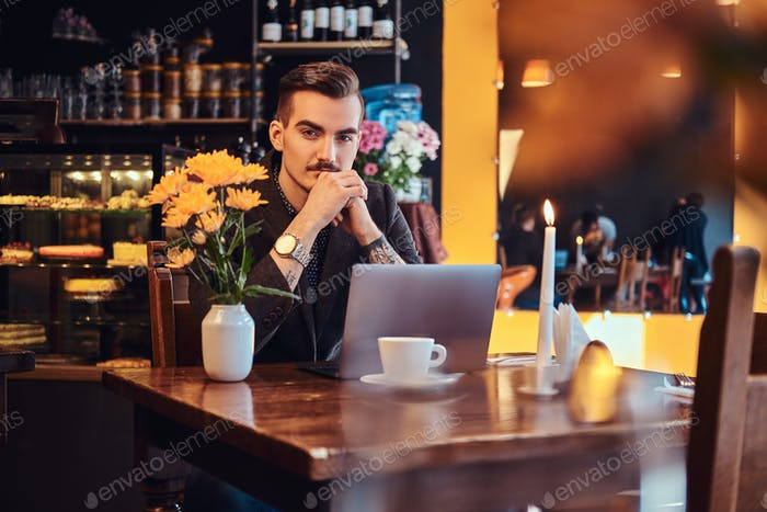 Portrait of a handsome businessman dressed in a black suit sitting in a cafe