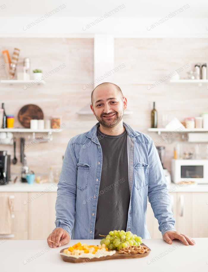 Guy standing at kitchen counter
