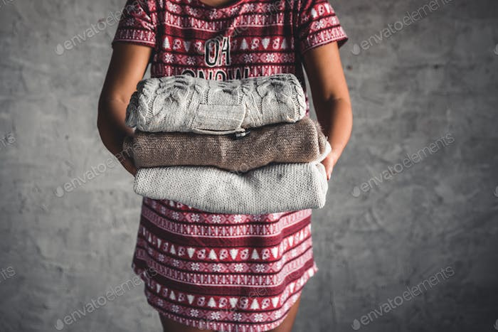 A girl in a Christmas dress holds a stack of sweaters. Warmth, comfort