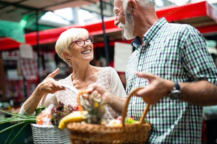 Senioren-Shopping-Paar mit Korb auf dem Markt. Gesunde Ernährung