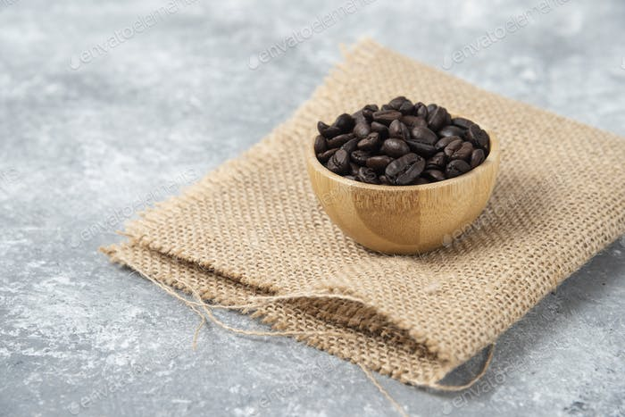 Roasted coffee beans in wooden bowl on marble background