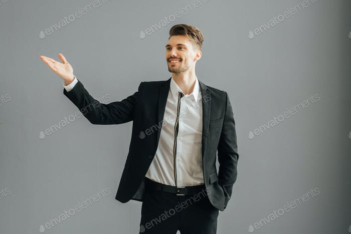 Success man in suit over gray wall. Successful male handsome guy portrait.