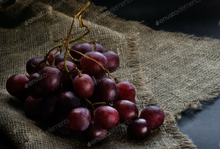Fresh red grapes over rustic background