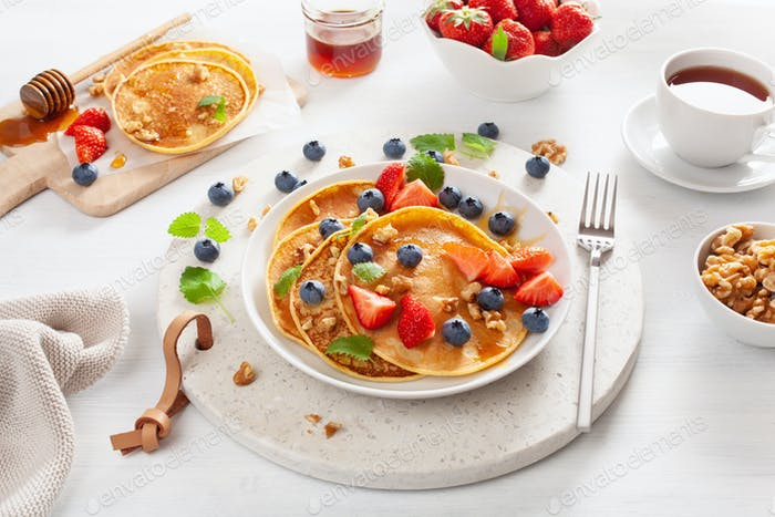 pancakes with blueberry strawberry honey and nuts for breakfast