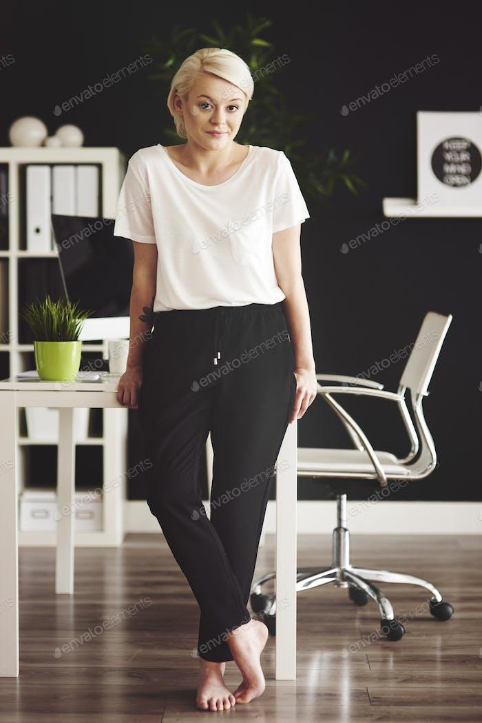Full-length portrait of barefoot businesswoman leaning against desk