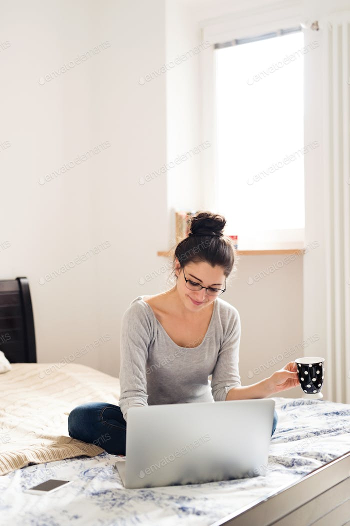 Beautiful young woman sitting on bed, working. Home office.