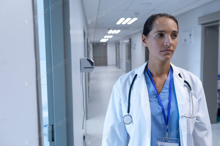 Front view of Caucasian female doctor standing in the corridor at hospital