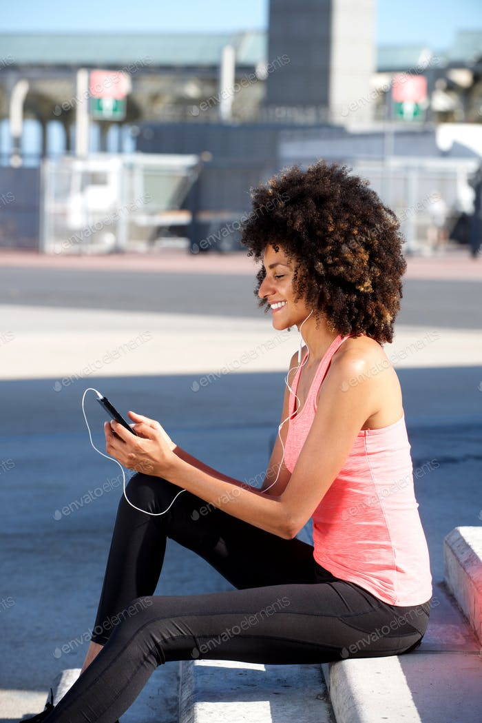 Beautiful woman sitting on steps listening to music on cellphone
