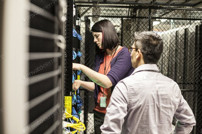 Caucasian woman and man technicians working on CAT 5 cables in a large computer server farm.