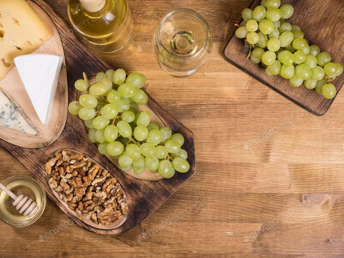 Thumbnail for Top view of wolnuts next to fresh grapes on wooden plate in a vintage restaurant