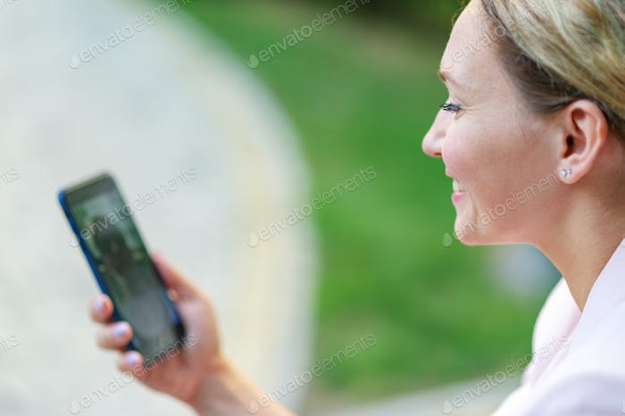 Woman has a video call by phone on the street