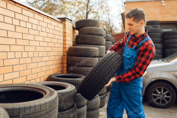 Male worker at the stack of tyres, tire service