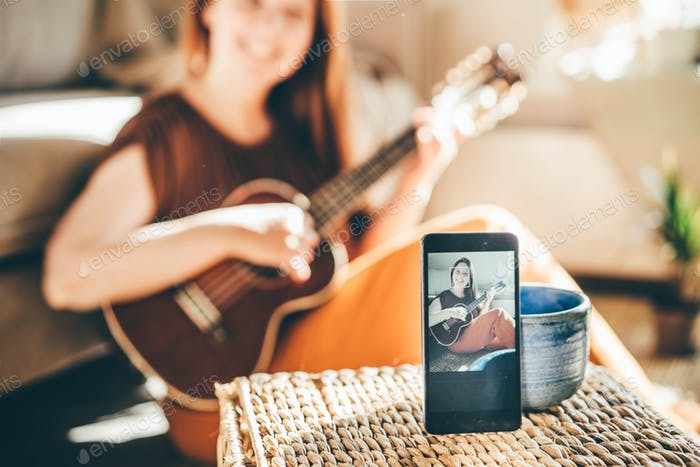 Selective focus on phone with video blogger playing on ukulele on phone screen.