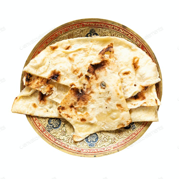 Naan flat bread on brass plate isolated