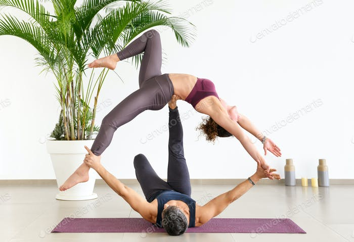 Two gymnasts doing an acroyoga pose