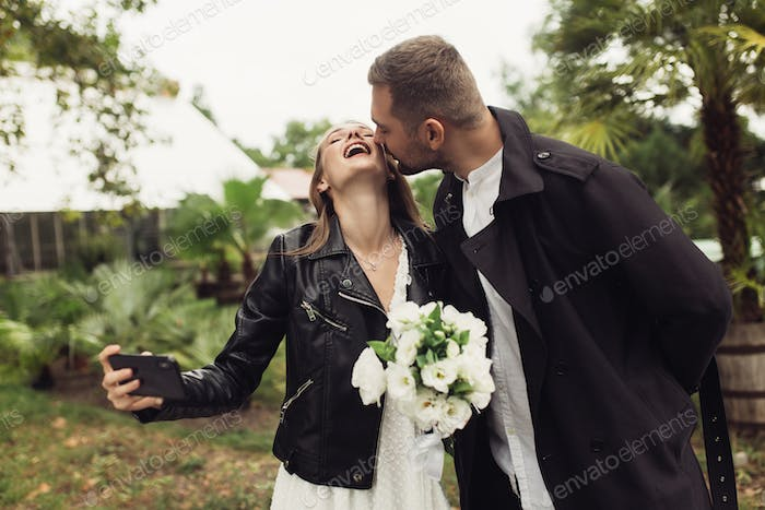 Young attractive man in trench coat kissing in cheek cheeful wom