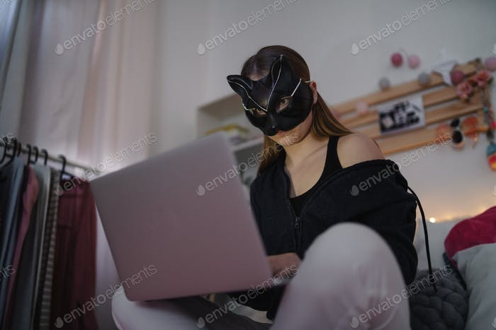 Young girl with cat mask and laptop sitting, online dating and abuse concept