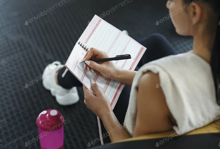 Junge Frau macht ihren Trainingsplan im Notebook drinnen, über Ansicht