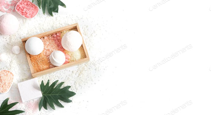 Composition with multi colored sea salt and bath bombs on a white background.