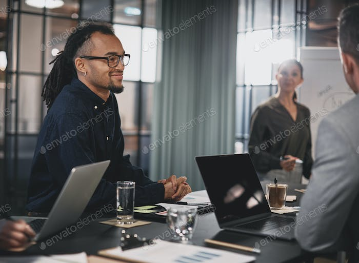 Smiling young businessman meeting with coworkers in an office