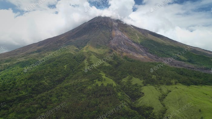 Closeup Philippines volcano top erupt clouds of haze aerial. Green grass mountain with hiking path