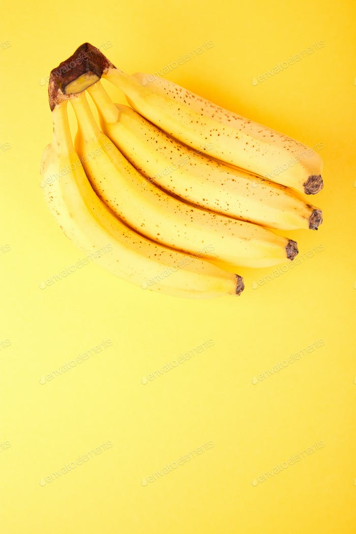 Banana on yellow paper background.