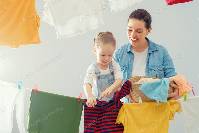 woman and girl hanging clothes on a rope