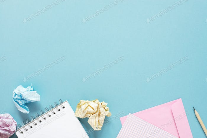 Blue Background with Notepads and Crumpled  Sheets of Paper