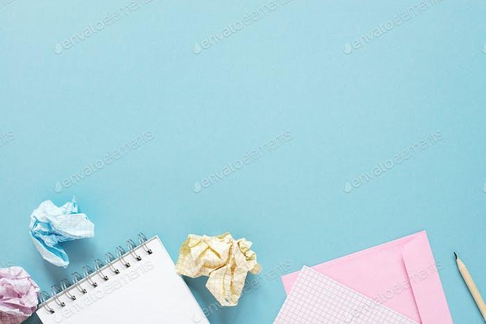 Fondo azul con blocs de notas y hojas de papel arrugadas