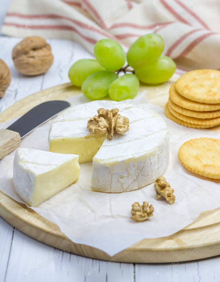Soft brie cheese with sweet grapes, nuts and crackers