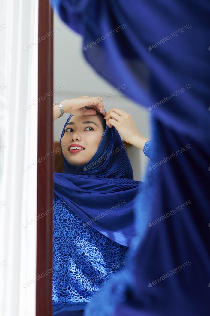 Woman putting on hijab