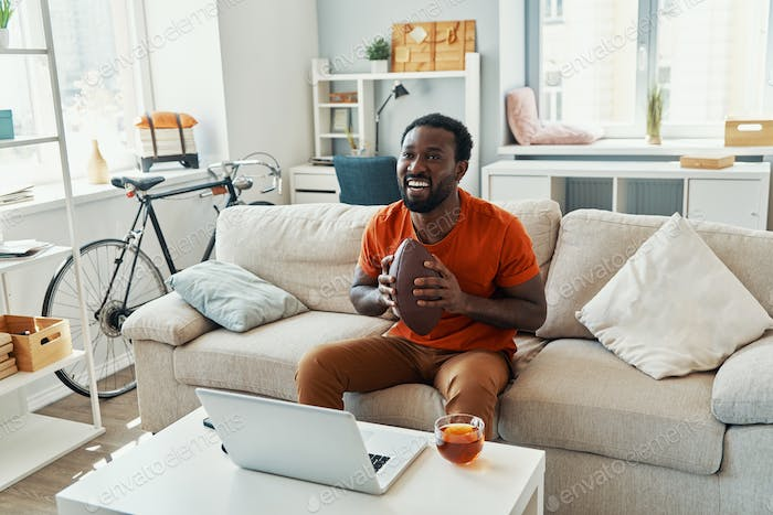 Happy young African man cheering and smiling while watching sport match at home