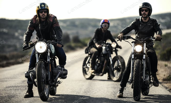 Three men wearing open face crash helmets and goggles sitting on cafe racer motorcycles on a rural