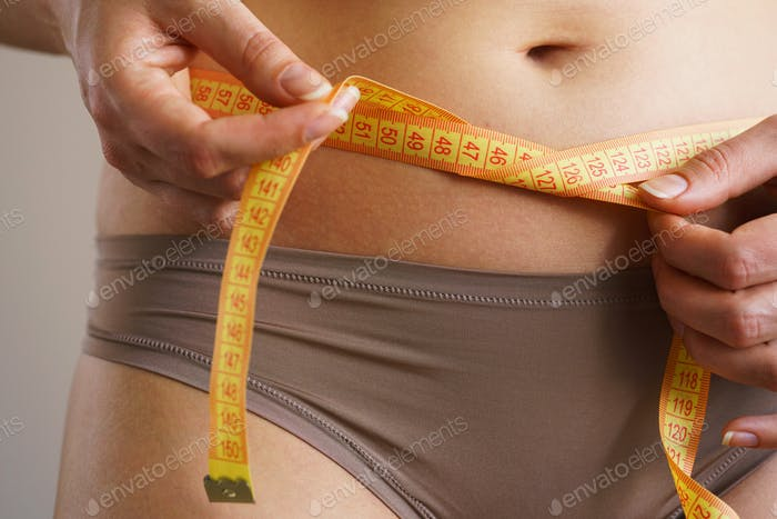 Woman measures a waist with a centimeter ribbon