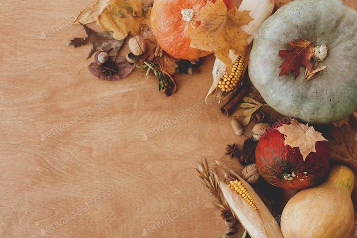 Pumpkins, autumn leaves, corn, walnuts,chestnuts,acorns on rustic wooden table