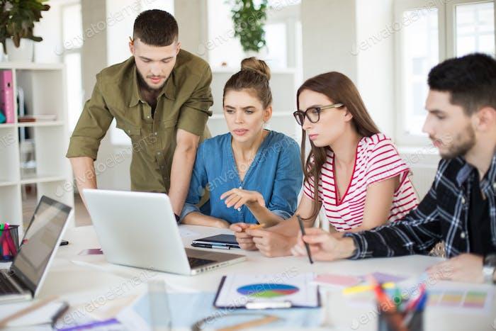 Группа молодых бизнесменов, вдумчиво использующих ноутбук вместе
