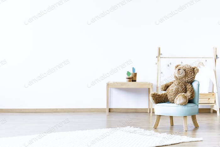 Teddy bear on blue chair in white boy's room interior with woode
