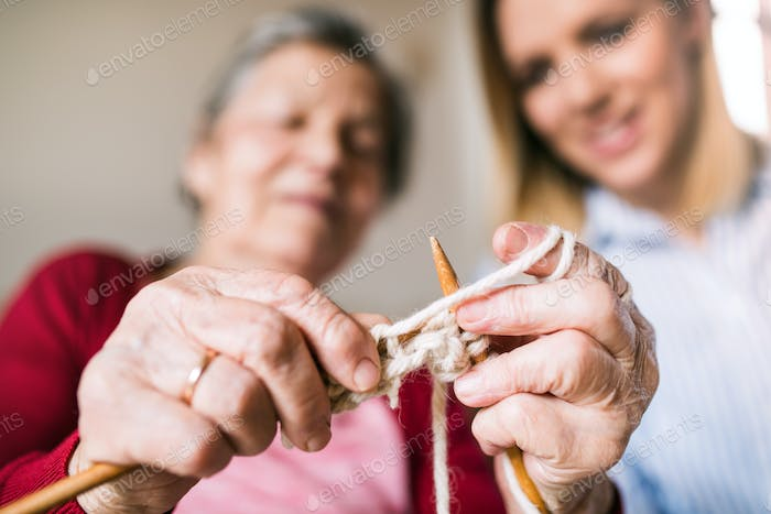 Elderly grandmother and adult granddaughter at home, knitting.