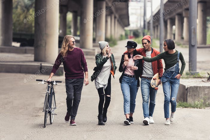 group of young stylish people walking outdoors