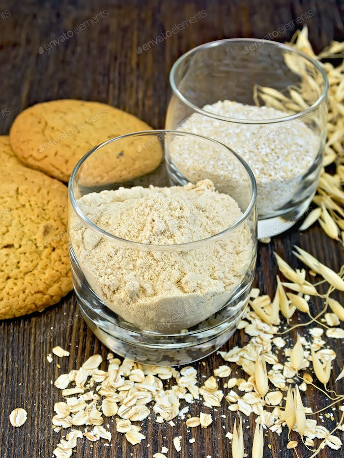 Flour and bran oat in glass with cookies on board