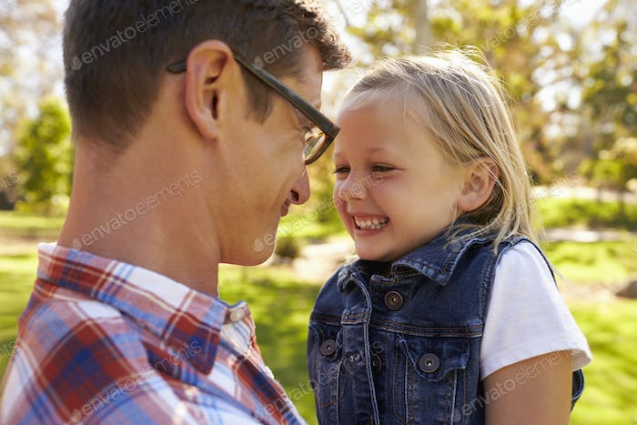 Dad and young daughter pulling faces at each other in a park